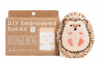 small DIY embroidered doll carton kit next to a hedgehog as a vegan gift idea