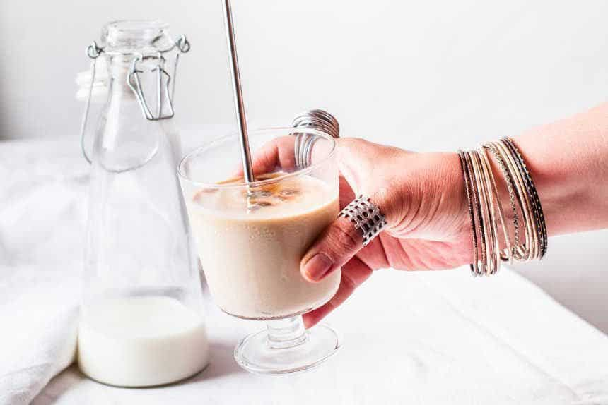 Woman with rings and bracelets holding glass with iced coffee with plant-based milk