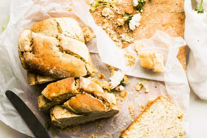 Rustic gluten-free bread with cut off slices on a wooden cutting board with white linen
