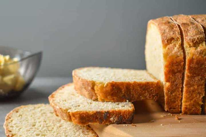Slices of vegan sandwich bread on a wooden cutting board with a grey backdrop