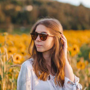 Woman in sunflower field wearing eco-friendly sunglasses