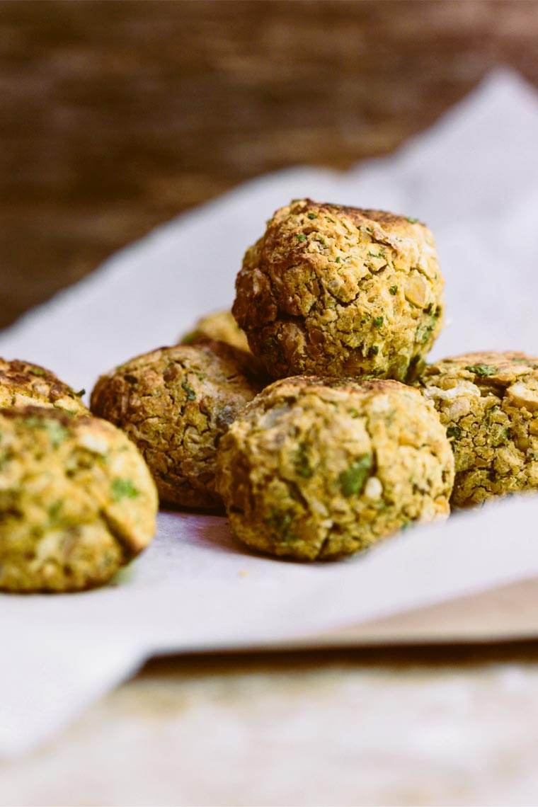 close up of seven freshly baked vegan falafel that are oil-free and golden brown on some parchment paper