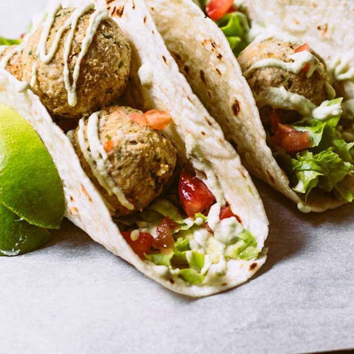 two taco shells that are filled with fresh veggies, baked falafel and drizzled with homemade vegan cashew sour cream