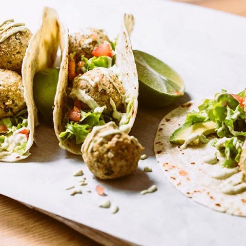 bright surface with three homemade healthy baked falafel tacos and some limes