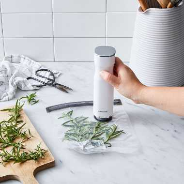 marble kitchen counter on which a hand uses a small tool to vacuum seal some fresh herbs