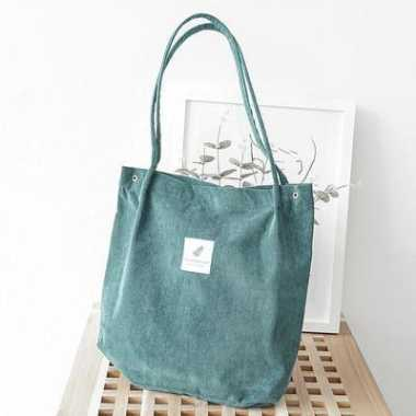 turquoise tote bag on a wooden box next to a white frame