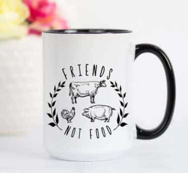 White mug with different cow, pig and chicken print as well as friends not food text