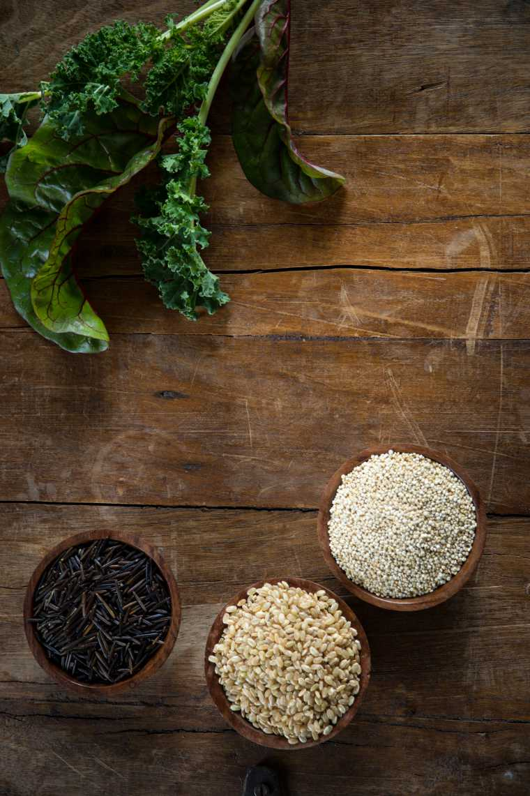 Small wood bowls filled with brown rice quinoa and wild rice on the left kale and Swiss chard on the right.