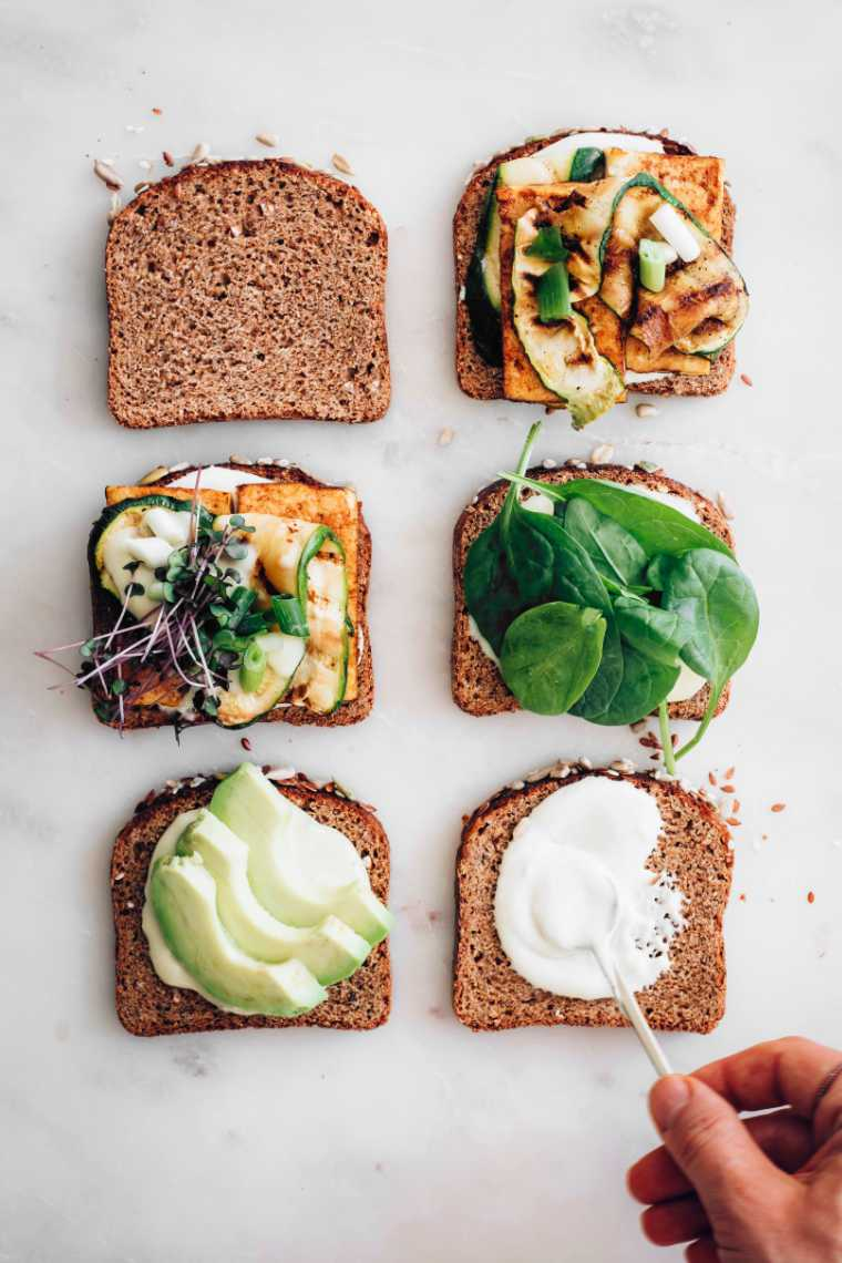 six slices of bread on a white table which are layered with vegan mayo, spinach, avocado, tofu and zucchini