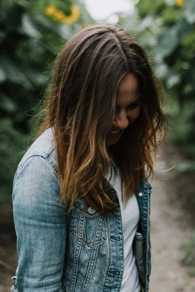 smiling brown haired woman with a jeans jacket standing in a sunflower field