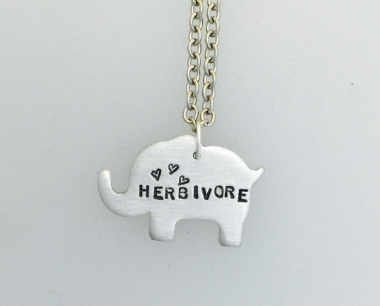 handmade necklace from etsy of an elephant with the word herbivore and some hearts