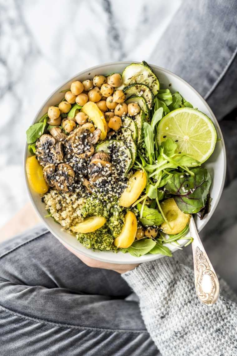 Woman sitting cross-legged and holding vegan buddha bowl with greens, chickpeas and other vegetables