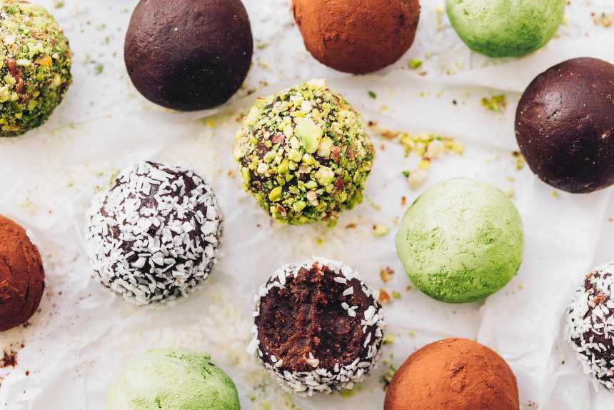 white parchment paper with chocolate, matcha, almond, pistachio and coconut bliss balls