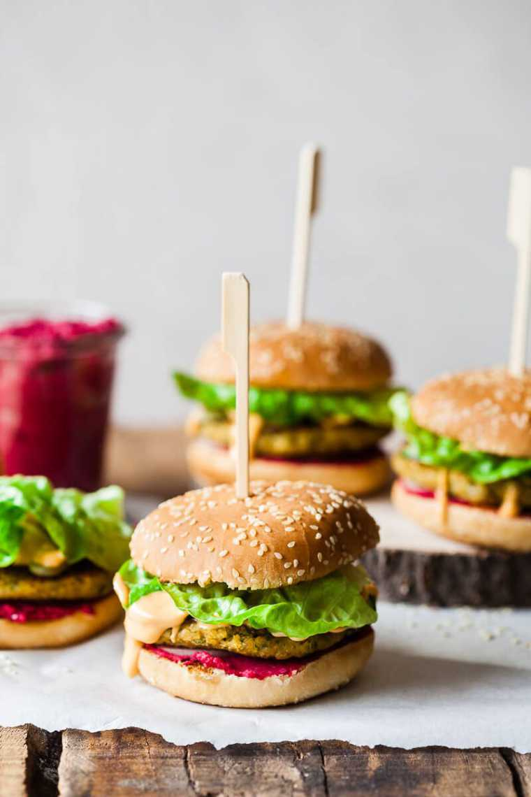 four plant-based burgers with lettuce, vegan patties and beet hummus on a wooden table