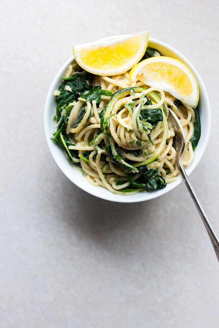 white bowl with pasta and green vegetables as well as two lemon wedges