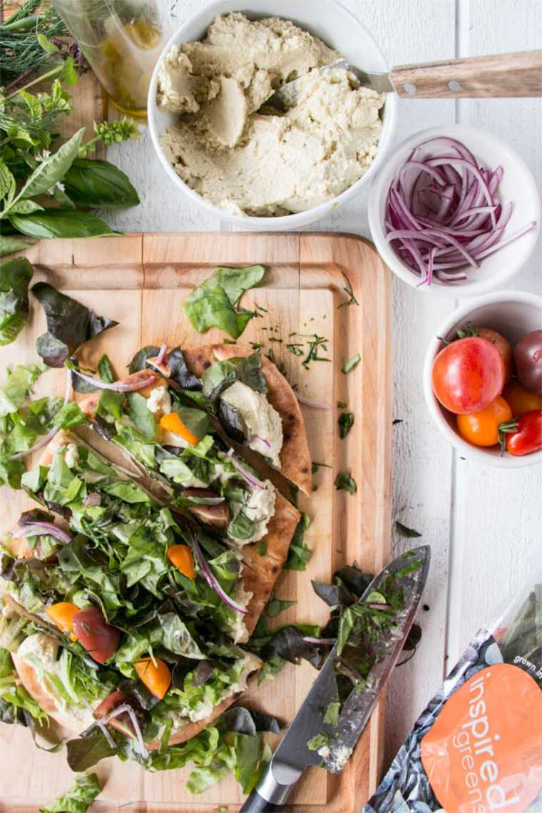 wooden chopping board with a flatbread that's spread with hummus, topped with veggies and cut into pieces