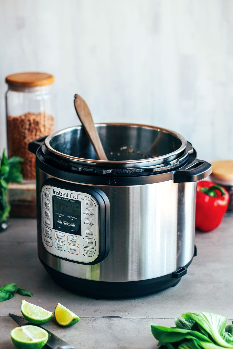 electric pressure cooker Instant Pot on table with a wooden spoon and vegetables
