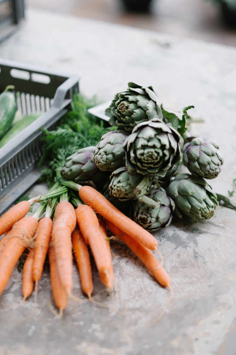 Bunch of carrots and artichokes as well as tray of cucumbers lying on gray concrete surface
