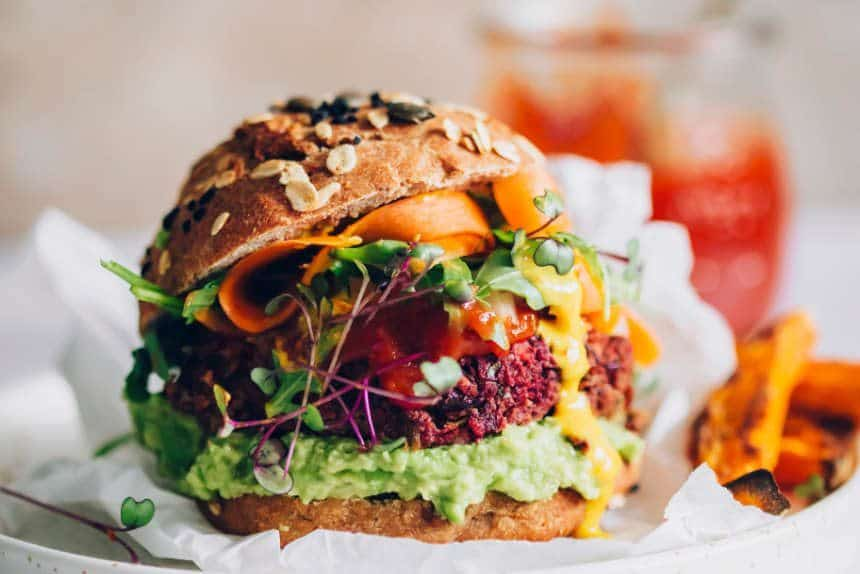 close up of colorful kidney bean beet burger in whole wheat bun with avocado, carrots and microgreens