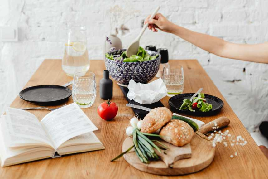 wooden table with a book, glasses, plates, different vegetables and white bread