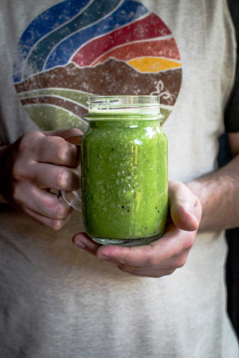 man in colorful shirt holding a glass with homemade green smoothie in his hands
