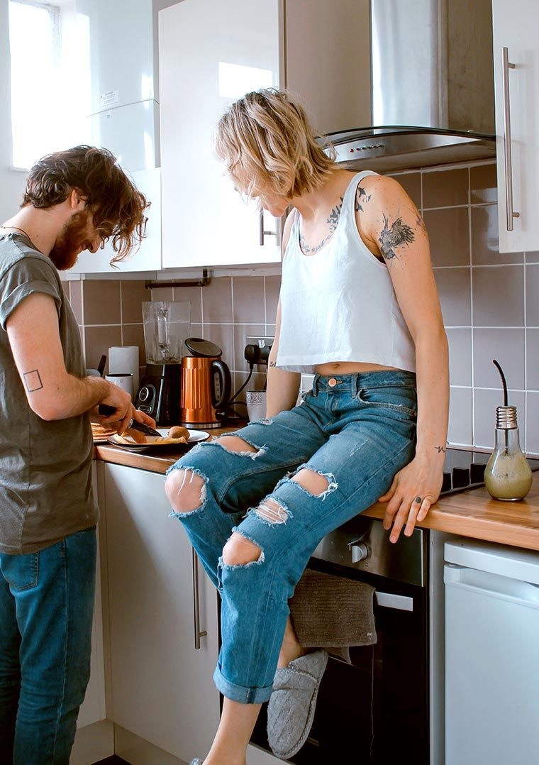 Man cutting vegetables in the kitchen next to a Woman in jeans sitting on the counter