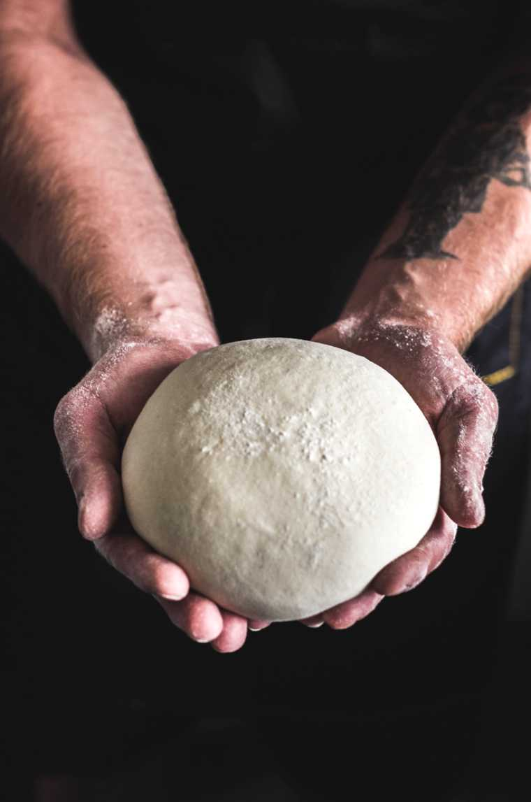 Man with black shirt holding bread dough in his hands