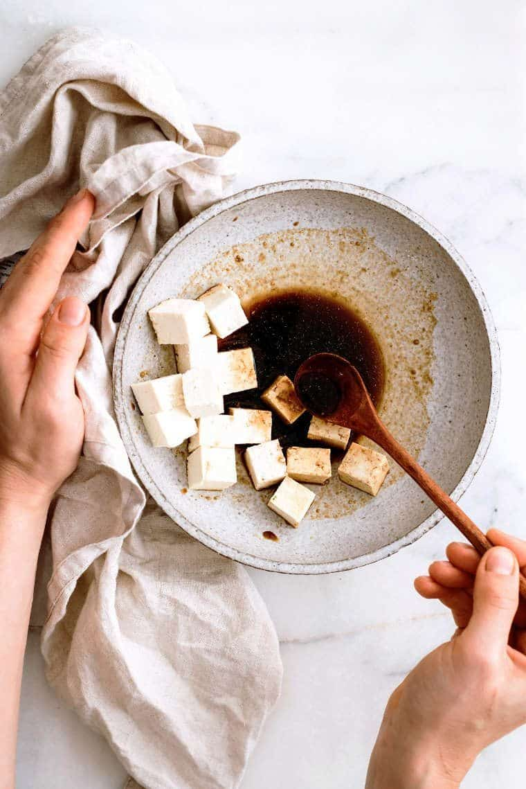 Woman using wooden spoon to mix cubed tofu with soy sauce