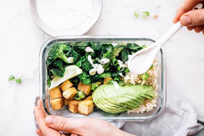 Woman drizzling white sauce over glass bowl filled with rice, avocado, broccoli, green onion and tofu