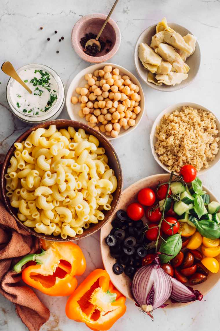 white table with different sized bowls containing cooked quinoa, chickpeas, artichokes, macaroni, bell pepper and salad veggies