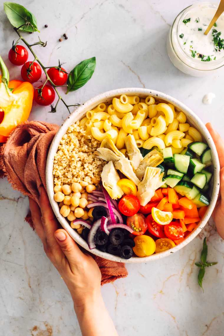 woman holding a large white bowl with quinoa, chickpeas, olives, pasta, cucumber and tomatoes