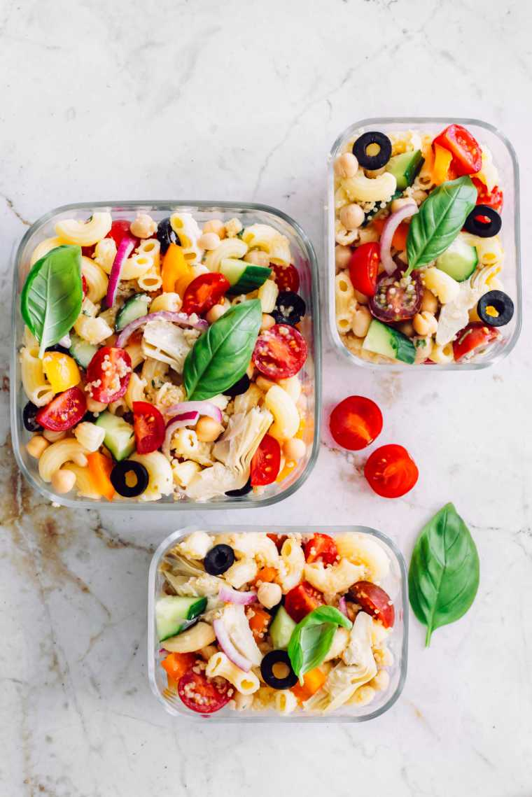 white tables with three glass containers containing colorful vegan quinoa pasta salad with tomatoes, bell pepper and basil