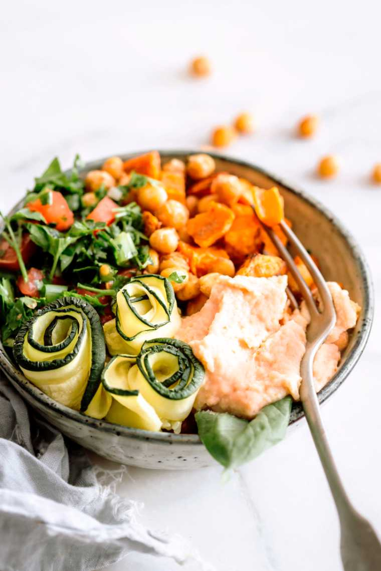 plant based bowl with chopped leafy greens, tomato, sweet potato cubes, chickpeas, zucchini and a dollop of homemade sundried tomato hummus next to a fork