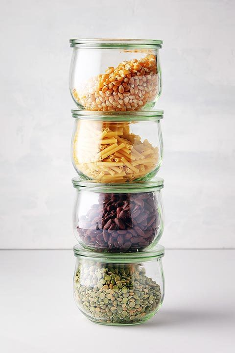 four glass jars of vegan staples such as corn, pasta, beans and lentils standing on top of each other