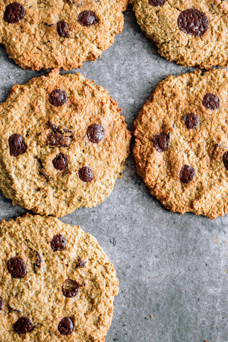 five gluten-free vegan oatmeal cookies with chocolate chips on grey surface