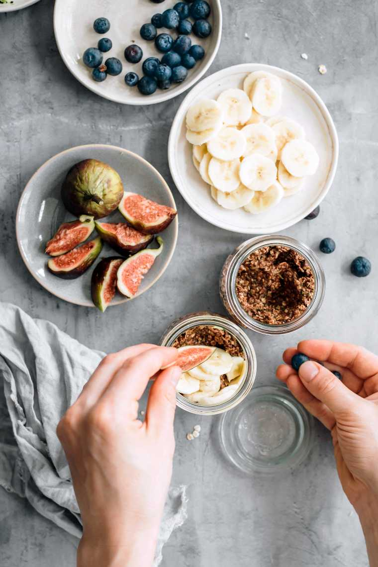 female hands placing some fresh fruit on chocolate overnight oats next to bowls of blueberries, sliced zucchini and fits