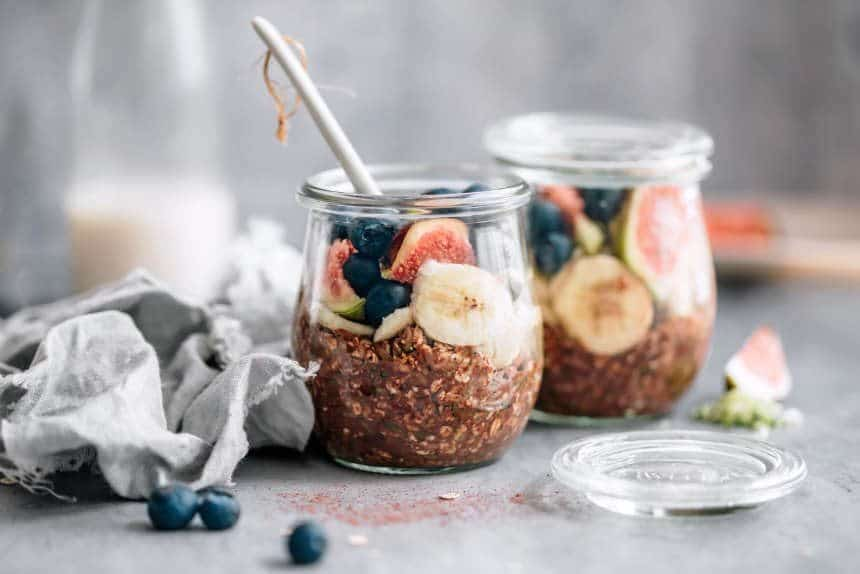 two glass jars of overnight zoats with sliced banana, figs and blueberries with a spoon in one of them