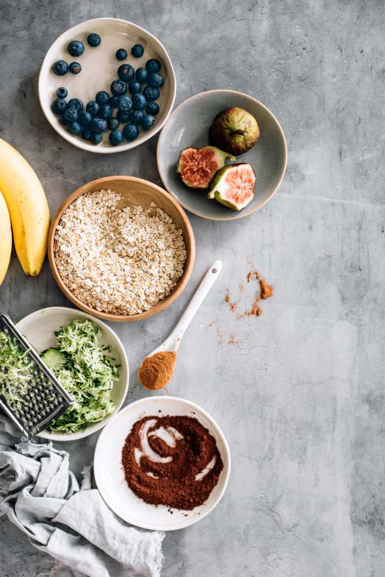top view of table with different-sized bowls with oats, shredded zucchini, figs, blueberries and cocoa powder