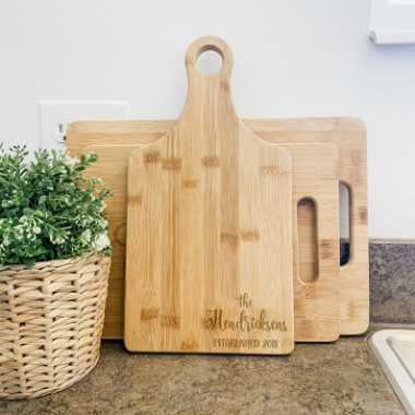 kitchen counter with a plant next to three different sized personalized bamboo cutting boards