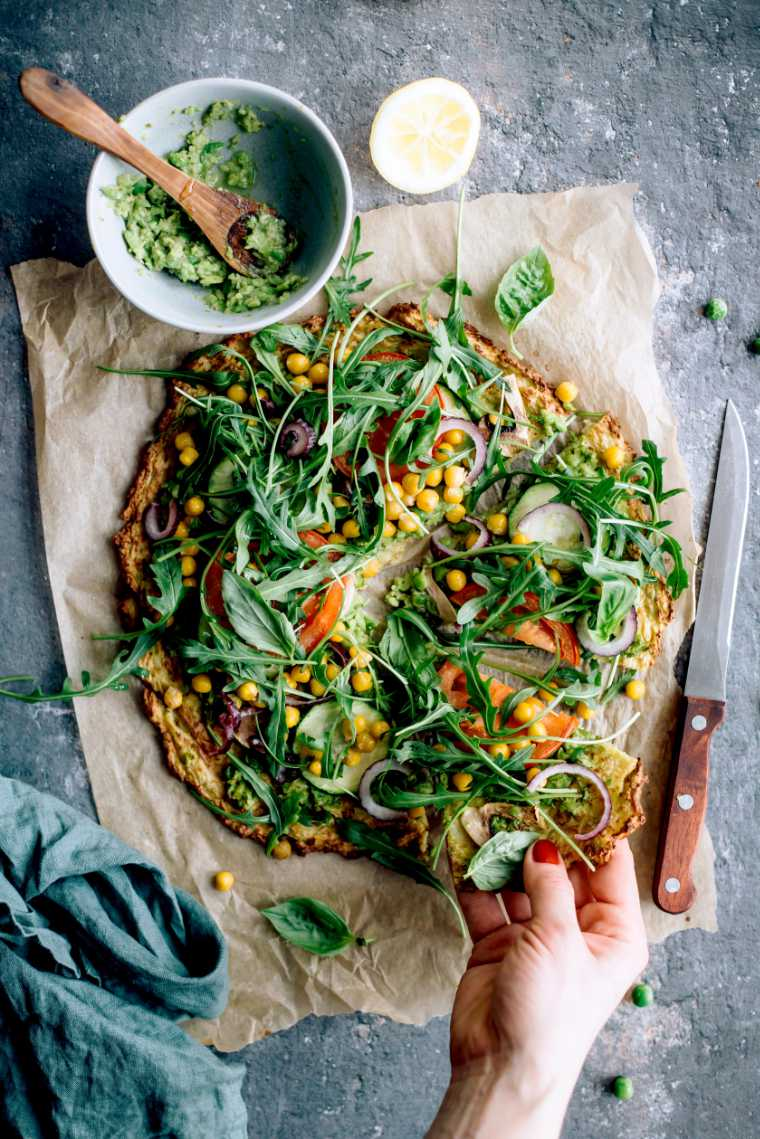baked vegan cauliflower crust pizza with veggies of which is one slice taken by a hand