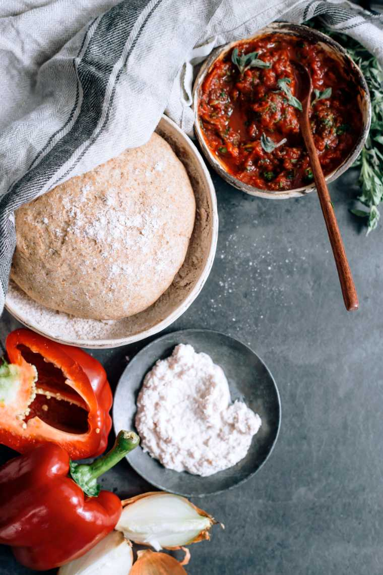grey table with onions, red bell pepper, tomato sauce and whole wheat dough in a bowl