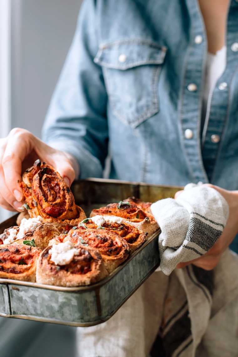 woman in jeans jacket holding a tray of freshly baked healthy vegan pizza rolls with almond ricotta and taking one to eat it