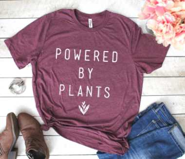 "purple colored cotton t shirt with the print ""powered by plants"" next to a pair of jeans and vegan shoes"