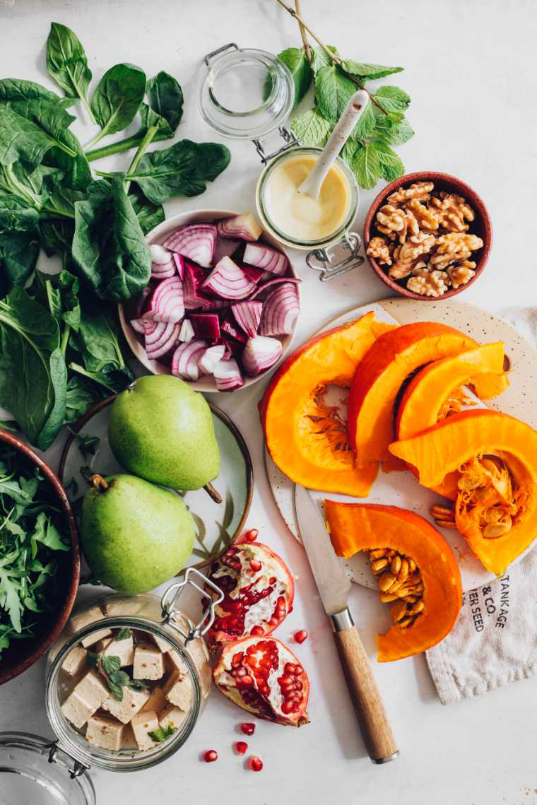 table with sliced pumpkin, red onion, walnuts, pomegranate, pear, spinach and tofu feta