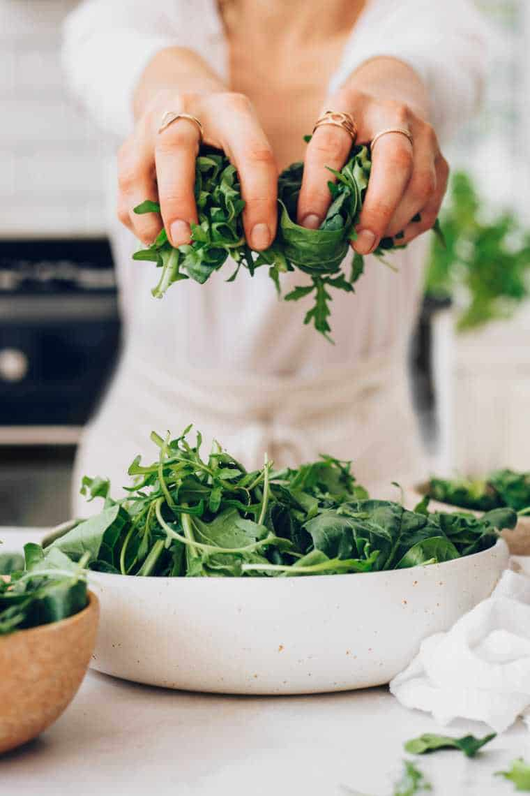 woman in white shirt and apron leaning over a table and holing fresh spinach and arugula in her hands