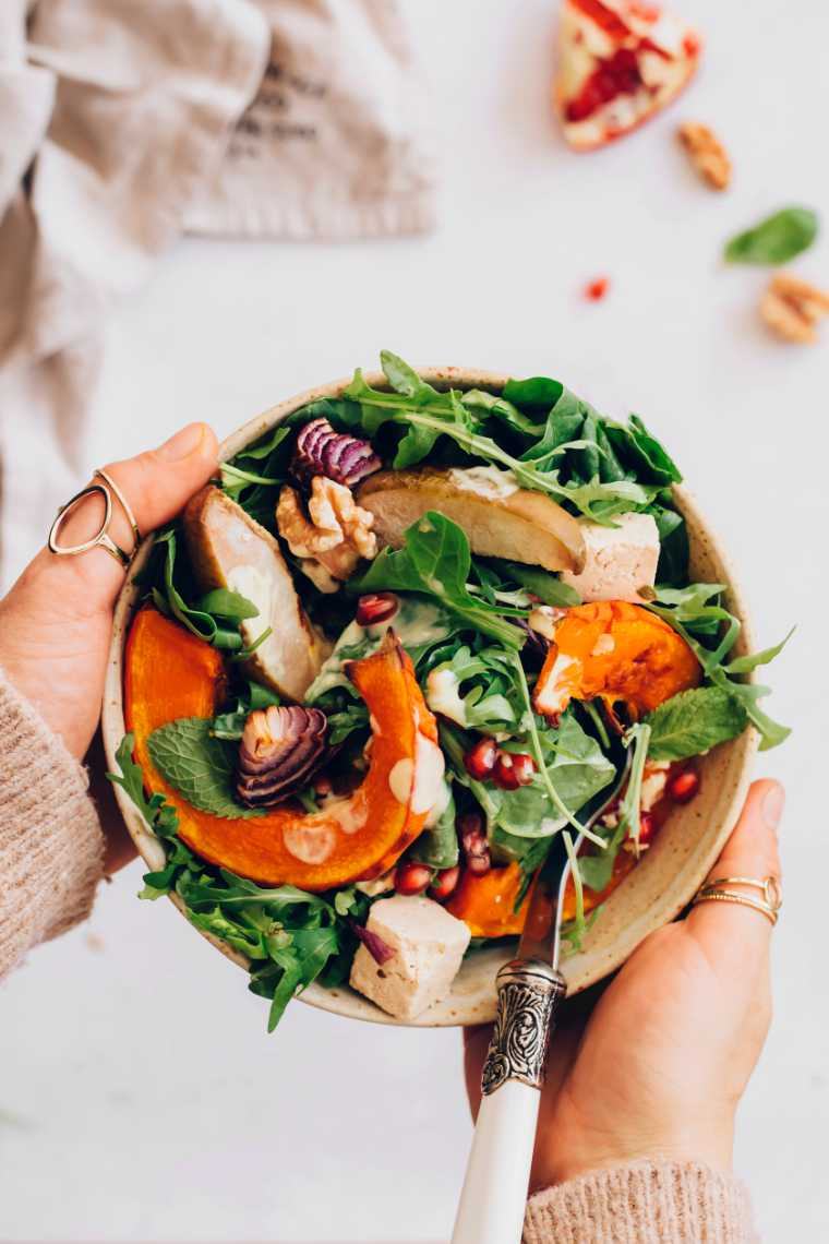 woman in brown sweater holding a small bowl of colorful spinach, pumpkin, feta and pear salad in her hands