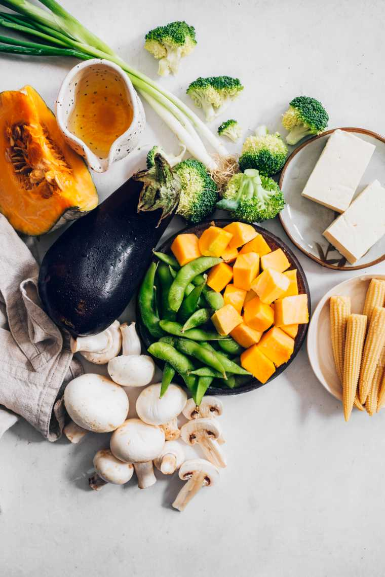 white table with white mushrooms, broccoli florets, green onions, eggplant, winter squash and tofu