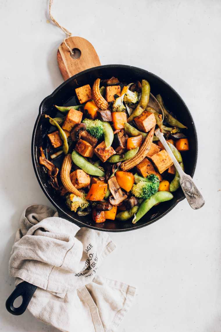 back pan on a chopping board with freshly cooked pumpkin stir fried vegetables