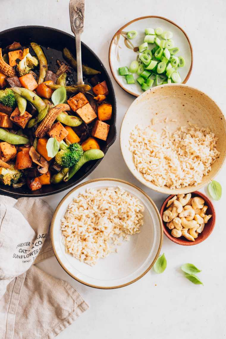 two bowls of brown rice next to some cashews and a black pan with vegetable stir fry