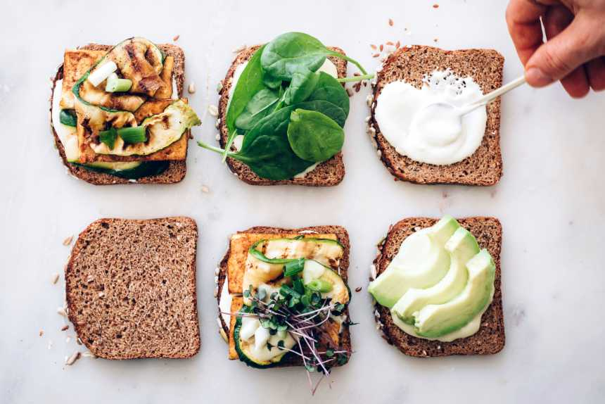 six pieces of dark bread with different toppings such as vegan cream cheese, avocado, greens and tofu